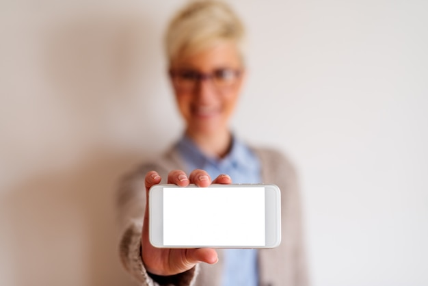 Close up of a focused view of a white cell phone with white screen . blurred picture of a girl behind the telephone holding it.