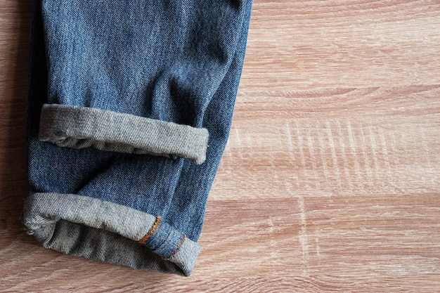 Close up of fold selvedge denim jeans on wooden background with copy space for text