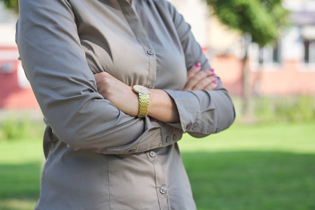Close up of folded arms of business woman