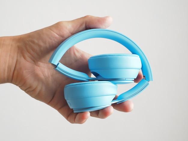 확대. 손에 접힌 파란색 헤드폰.