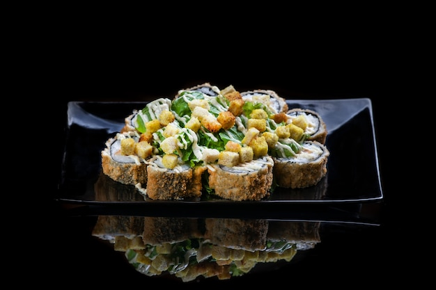 A close up of food fried sushi rolls isolated on black reflection