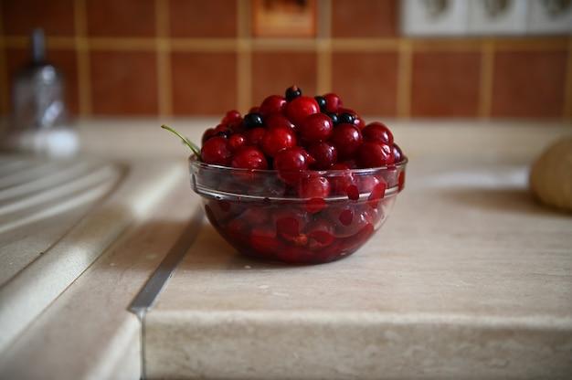 キッチンカウンターの透明なガラスのボウルに新鮮で甘くてすぐに食べられる熟したチェリーベリーのクローズアップ食品の写真。ハイアングルビュー