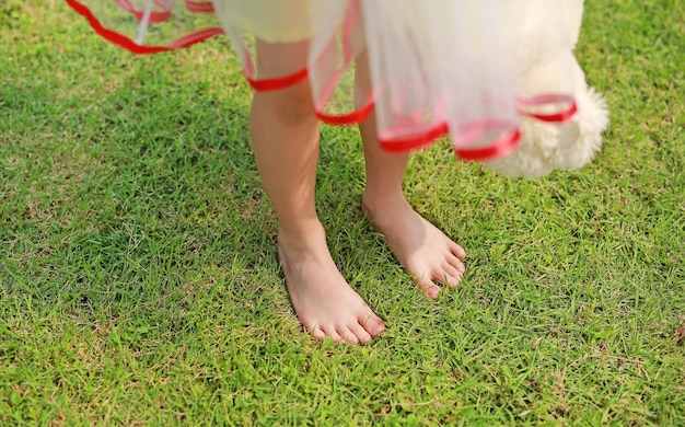 Close-up foot of child girl standing on green grass field.