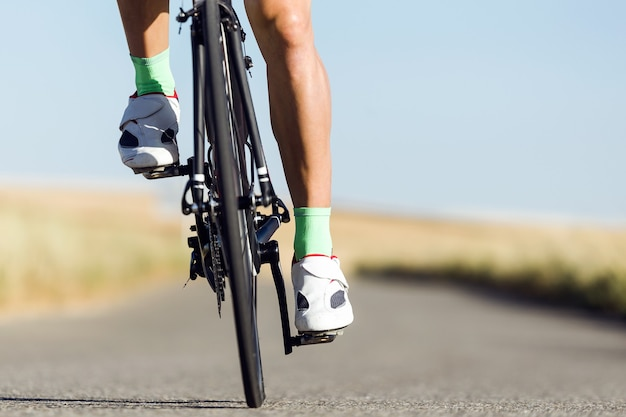 Close-up of the foot of a young man cycling on the road.