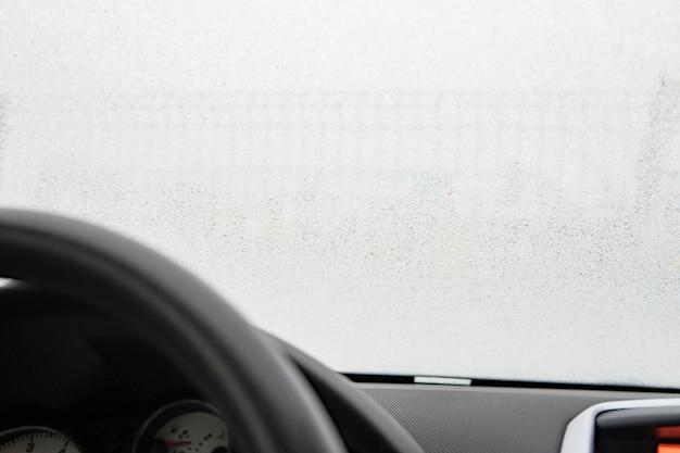 車のフロントガラスの映像をクローズアップし、車のフロントガラスに霜が降ります。運転席側からの眺め
