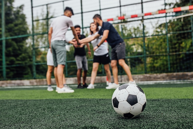 Primo piano del pallone da calcio sul campo verde.. giocatori che vanno a giocare insieme..