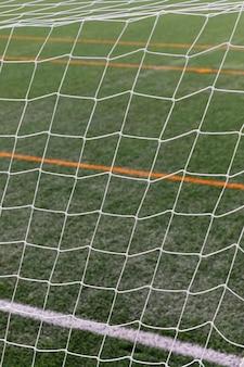 Закройте футбольное поле с сеткой