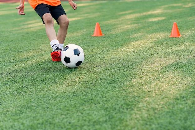 Close up footballer feet kicking ball on grass.
