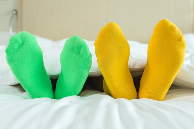 Close up foots of family with color sock on the bed