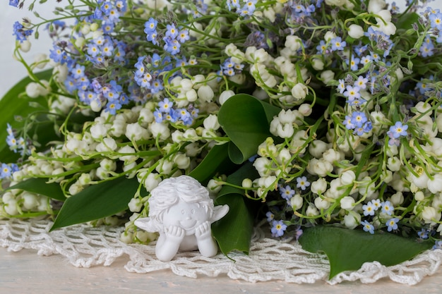 Close up forget me nots, lilies of the valley and white angel