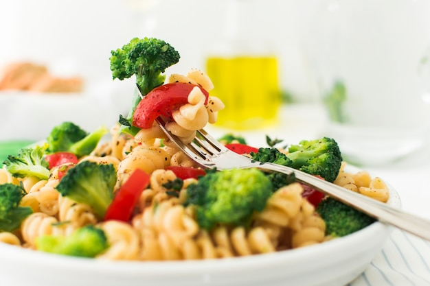 Close-up of fork with broccoli; tomato and fusilli in white plate