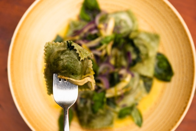 Close-up of fork with green ravioli pasta in plate
