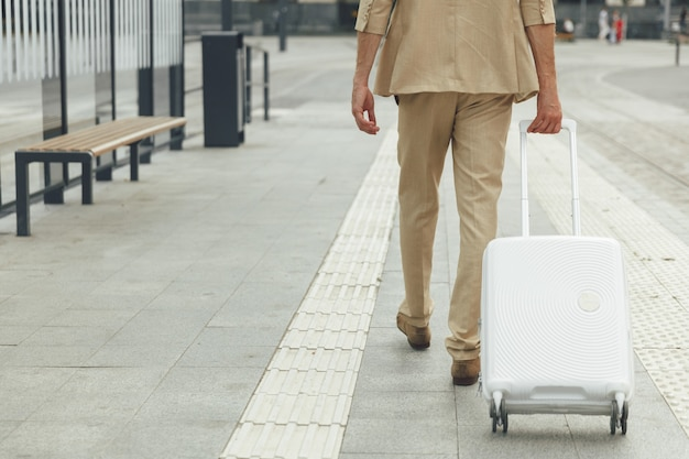 Close up of formally dressed male wheeling white suitcase at bus station. business travel concept