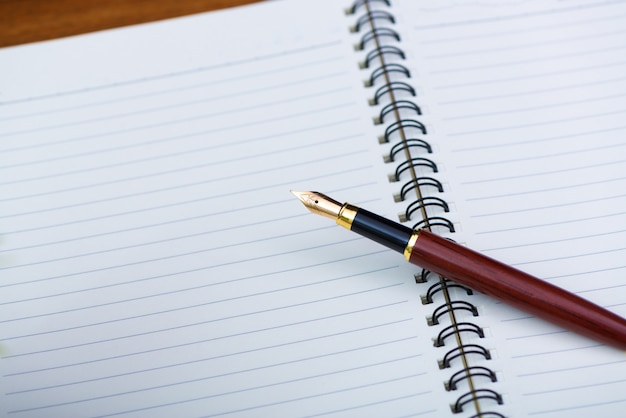 Close up of fountain pen or ink pen with notebook paper