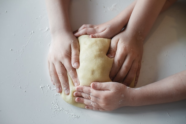 Close up. four children's hands, pressing the dough to the white table. preparation of desserts.