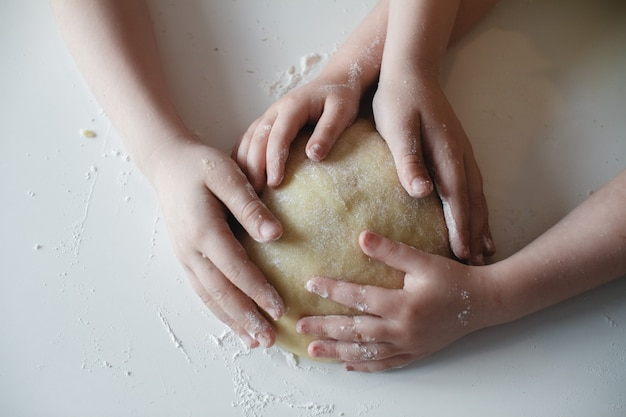 Close up. four children's hands, pressing the dough to the white table.