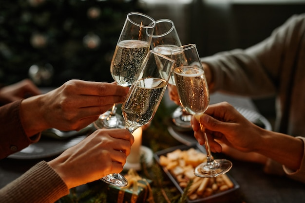 Close up of four people enjoying christmas dinner together and toasting with champagne glasses while...