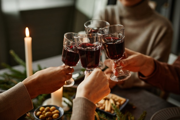 Close up of four people enjoying christmas dinner together and toasting with wine glasses while sitt...