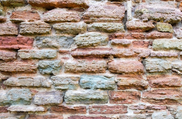 Close-up of a fragment of an ancient historical medieval stone wall.