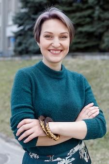 여성 모직 스웨터의 클로즈업 조각입니다. 녹색 니트 드레스에 아름 다운 소녀입니다. 녹색 니트 스웨터. 세련되게 옷을 입은 소녀. 여성의 겨울 따뜻한 옷.