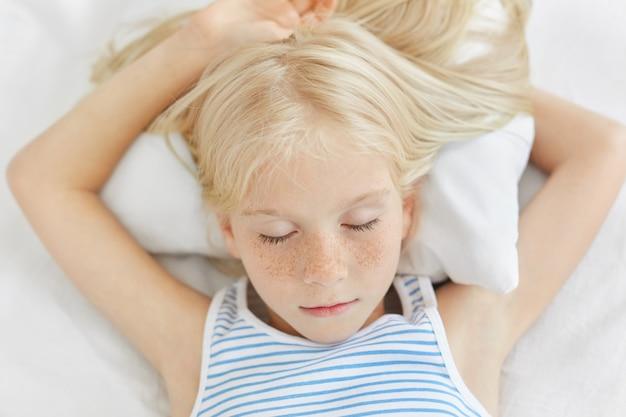 Chiuda in su della ragazza lentigginosa con capelli biondi sdraiato su lenzuola bianche, dormire di notte e avere sogni piacevoli. piccolo bambino femmina sognare ad occhi aperti. realxed bambina chiudendo gli occhi, sentendo il rilassamento