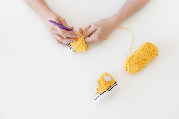 Close up of a freelance woman sewing cute baby bootees