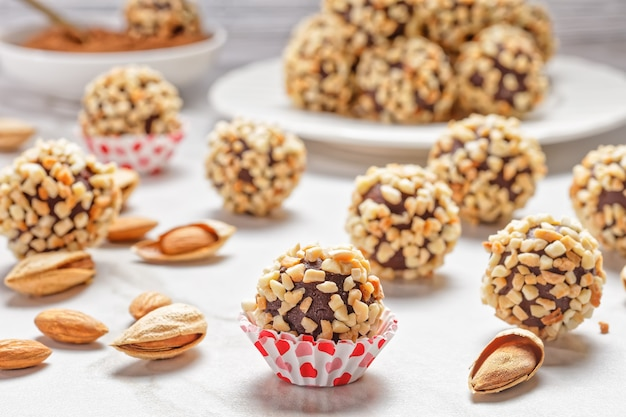 Close-up on french dark chocolate truffles coated with crushed almonds served on a white marble stone background, top view