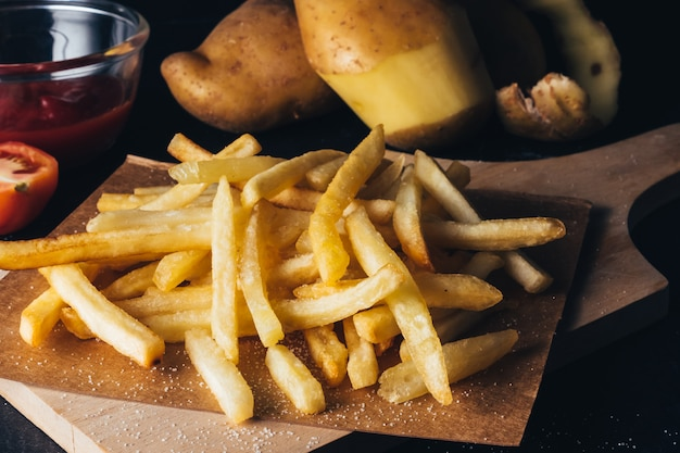 Close up of french fries with ketchup and raw potatoes on black bacground.