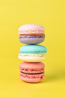 Закройте вверх по французскому macaron на желтом фоне.