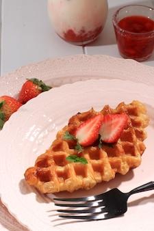 딸기를 얹은 분홍색 접시에 신선한 구운 일반 크로플 크루아상 와플을 닫습니다. 한국 딸기 우유와 함께 제공