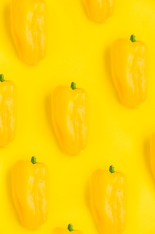 Close-up of fresh bell peppers on yellow backdrop