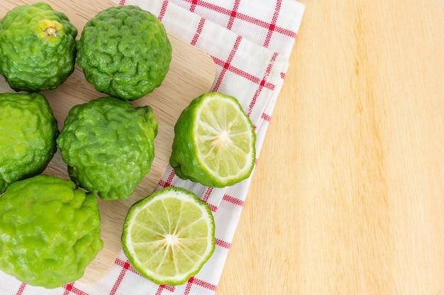 Close up fresh bergamot and bergamot slice on dark wood table background