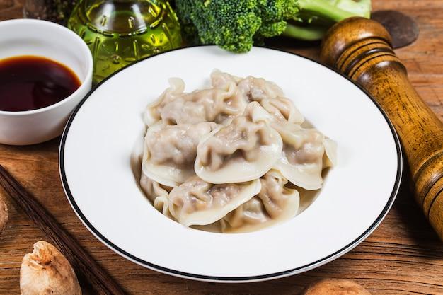 新鮮なゆで餃子を木のプレートの熱い蒸気で閉じます。