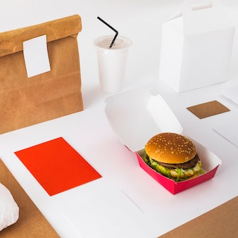 Close-up of fresh burger with disposal cup and food parcel