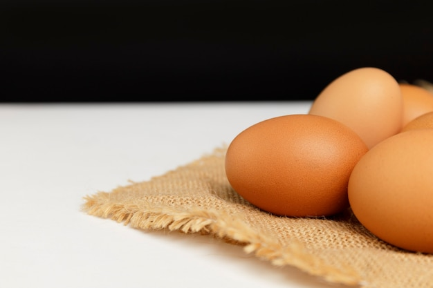 Close up fresh chicken eggs on linen tablecloth and white table