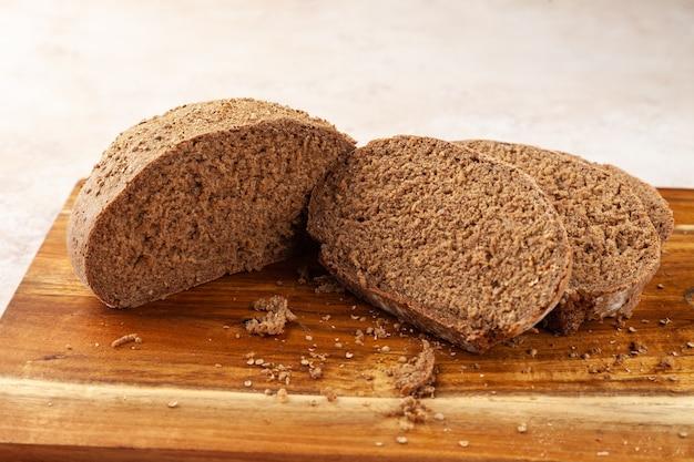 근접 신선한 다진 갈색 호밀 빵, 나무 커팅 보드에 조각