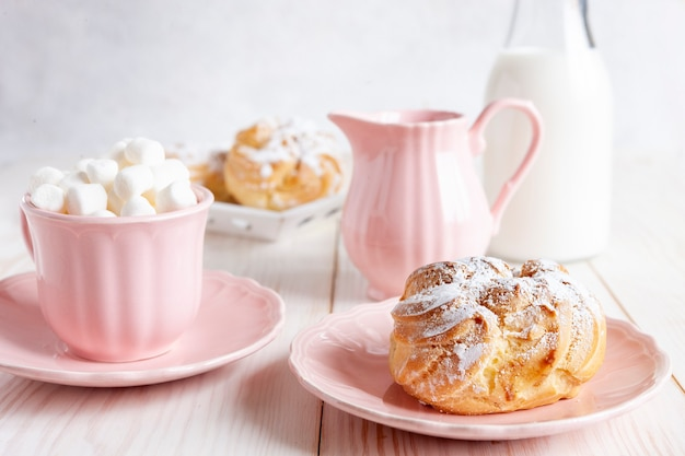 Close-up of fresh cream buns and  pink cup with hot drink and marshmallows