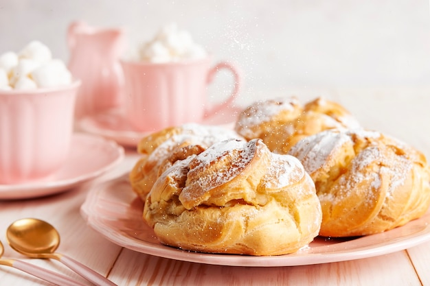 Close-up of fresh cream buns and two pink cups with hot drink and marshmallows