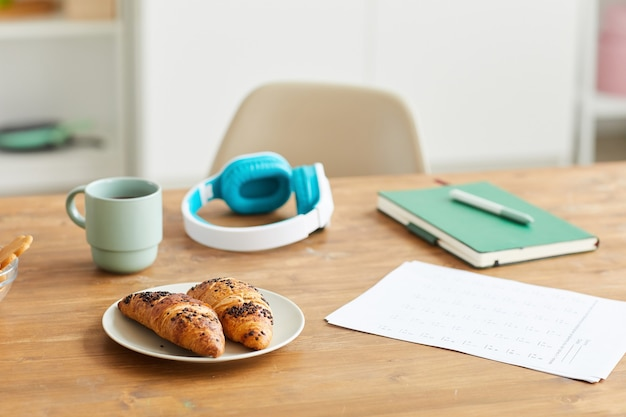 Close-up of fresh croissants on the plate served with coffee during coffee break after study