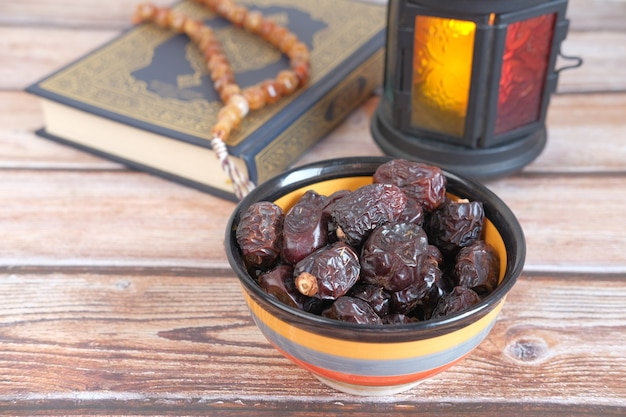 Close up of fresh date fruit in a bowl and quran on desk
