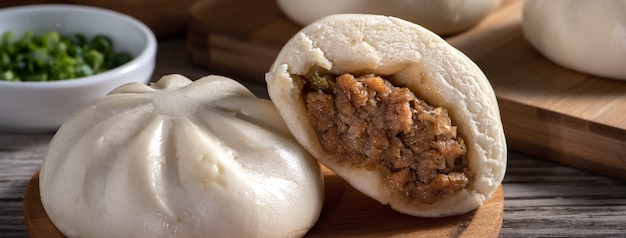 Close up of fresh delicious baozi, chinese steamed meat bun is ready to eat on serving plate and steamer, close up, copy space product design concept.