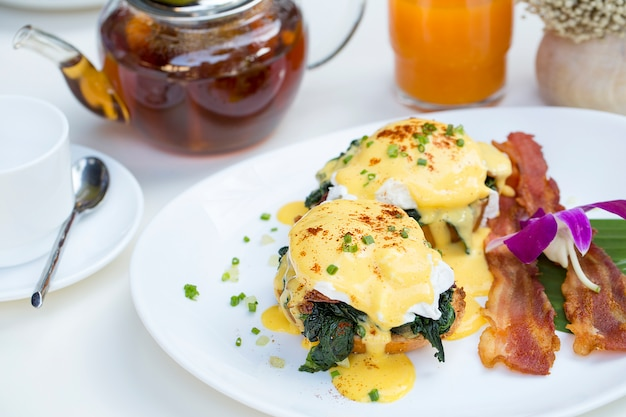 Close up fresh egg benedict breakfast with black coffee and orange juice