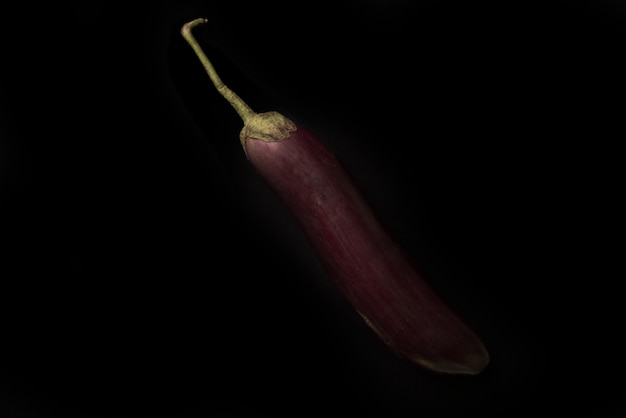 Close up of a fresh eggplant isolated over black