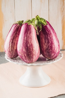 Close-up of fresh eggplants arranged on cake stand