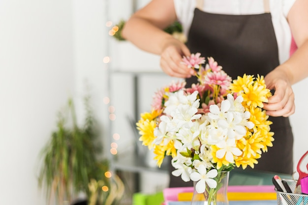 Close-up of fresh flowers in front of female florist