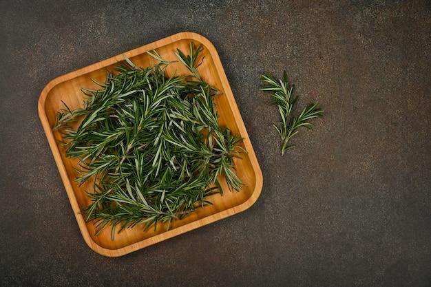 테이블에 대나무 나무 접시에 신선한 녹색 로즈마리 잎을 닫습니다.