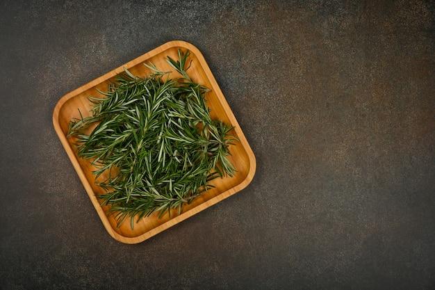 테이블에 있는 대나무 나무 접시에 신선한 녹색 로즈마리 잎을 닫고 바로 위에 있는 위쪽 전망