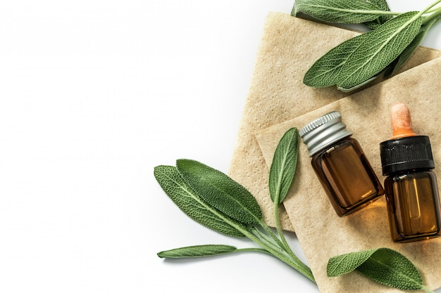 Close up fresh green sage herb leaf with a bottle of essential oil on white background , herb essence