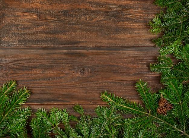 복사 공간이 있는 짙은 갈색 나무 판자 배경 위에 원뿔이 있는 신선한 녹색 가문비나무 또는 소나무 크리스마스 나무 가지를 닫습니다