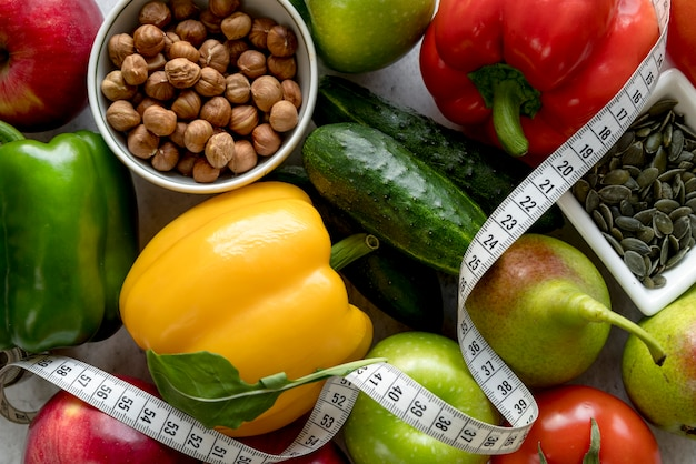 Close-up of fresh healthy fruits and vegetables with measuring tape